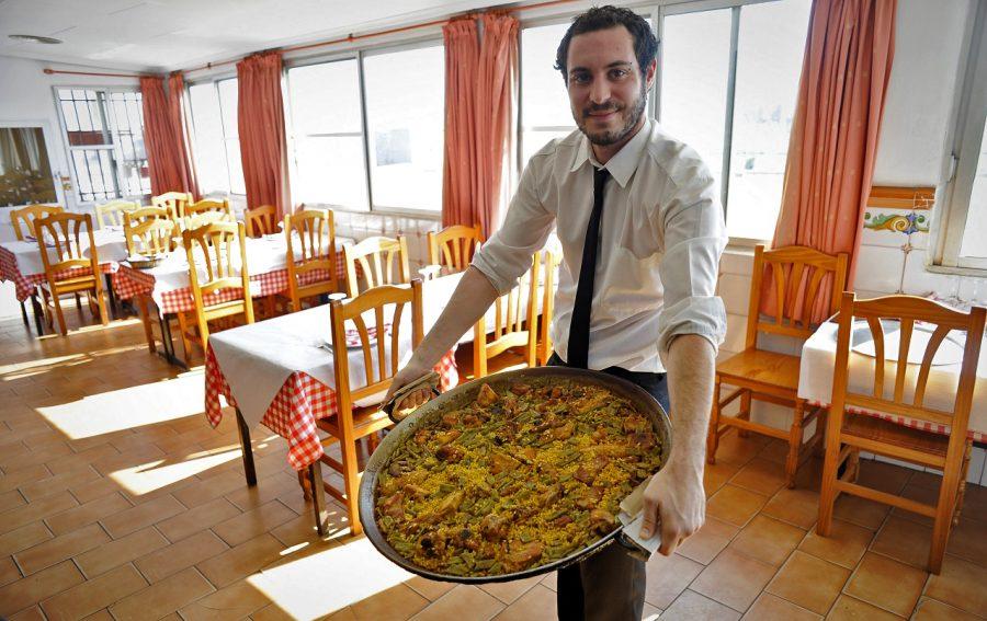 A waiter transporting his huge pan of paella